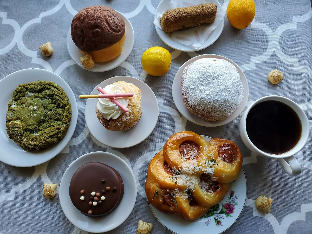 A Sunday Bakeshop pastry box with a strawberry Pocky muffin, hot dog sausage bun, banana milk doughnut, lemon-black tea Twinkie and other sweets.