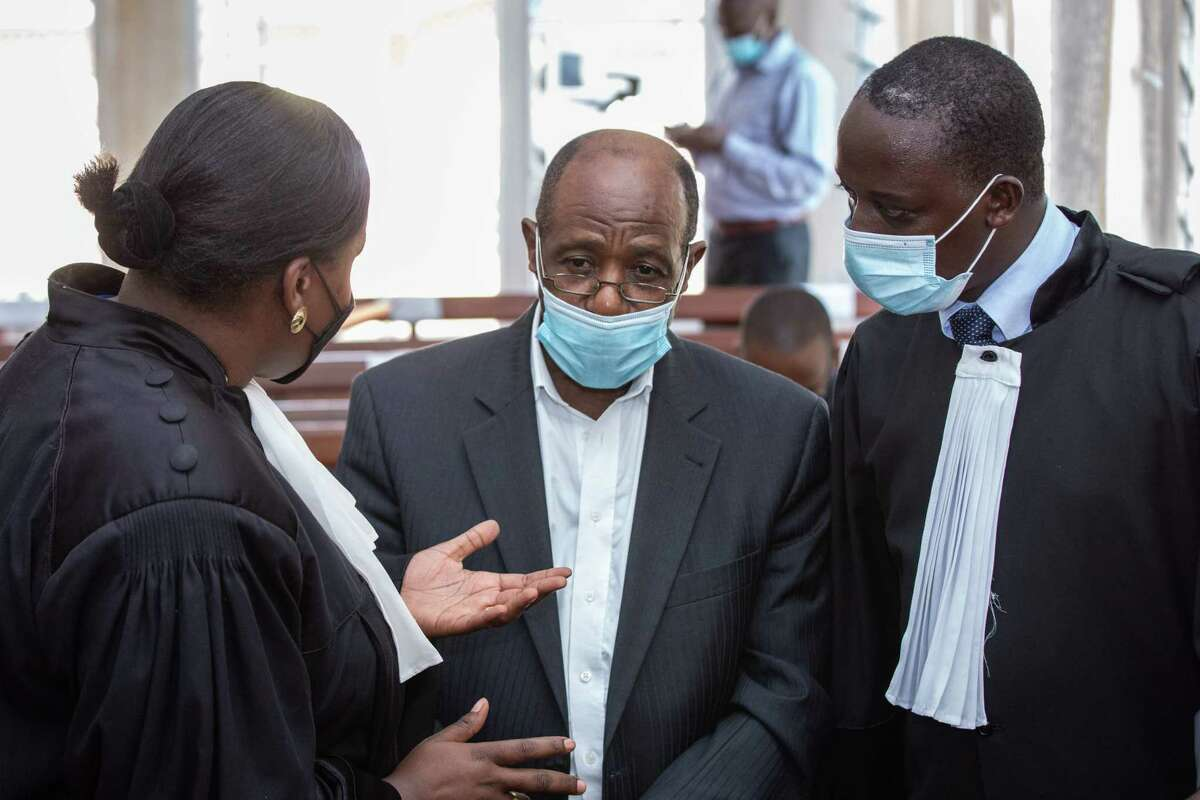 """""""Hotel Rwanda"""" hero Paul Rusesabagina (center) speaks with his lawyers at the Kicukiro Primary Court in Kigali, Rwanda, last September, when he was denied bail on terrorism charges."""