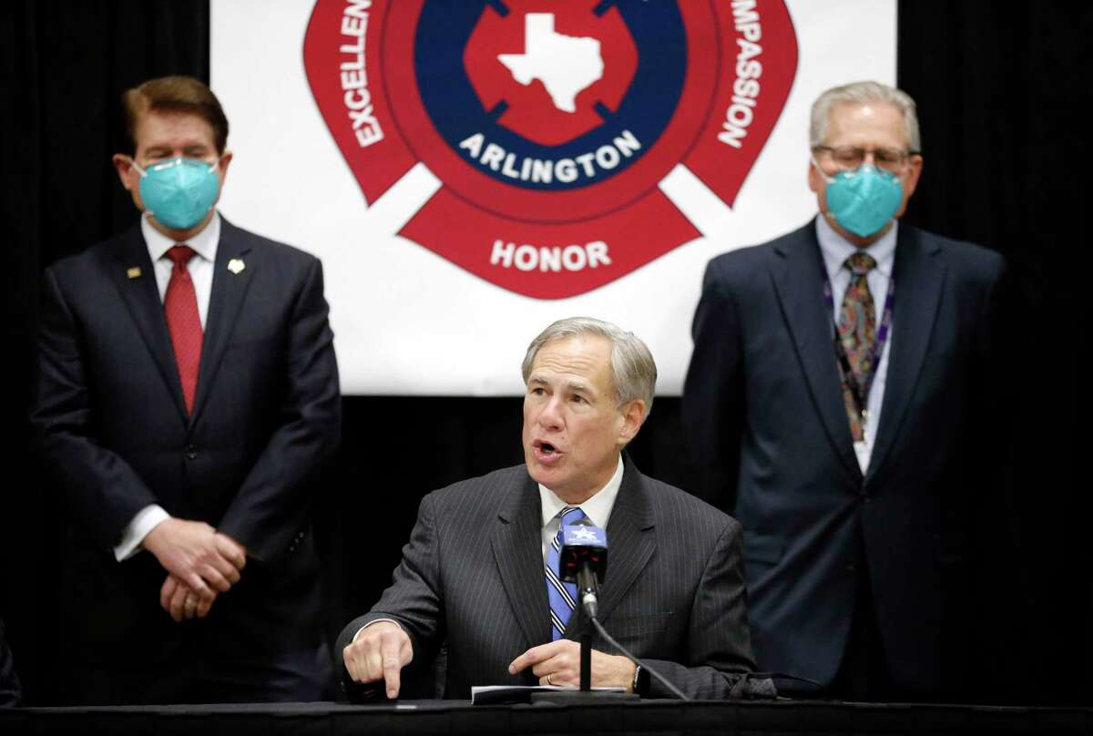 Texas Governor Greg Abbott makes remarks during a press conference at the Esports Stadium Arlington & Expo Center, a mass COVID-19 vaccination site in Arlington, Texas, Monday, January 11, 2021. Joining him in an earlier briefing and tour were Arlington Mayor Jeff Williams (left) and Texas Health Resources CEO Barclay E. Berdan. (Tom Fox/The Dallas Morning News)