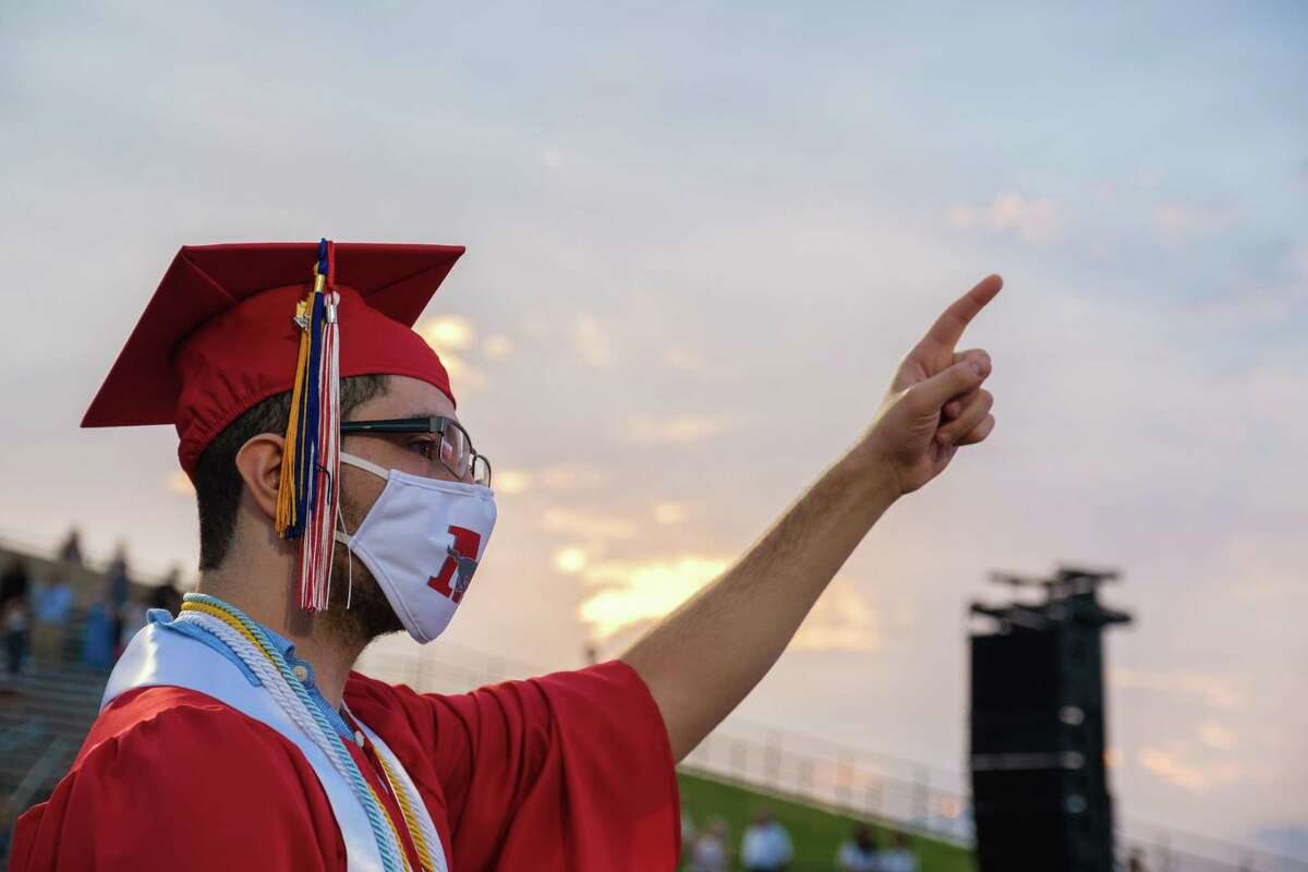 A Memorial High School senior joins in the singing of the school song at the end of the graduation ceremony at Darrell Tully Stadium on June 1