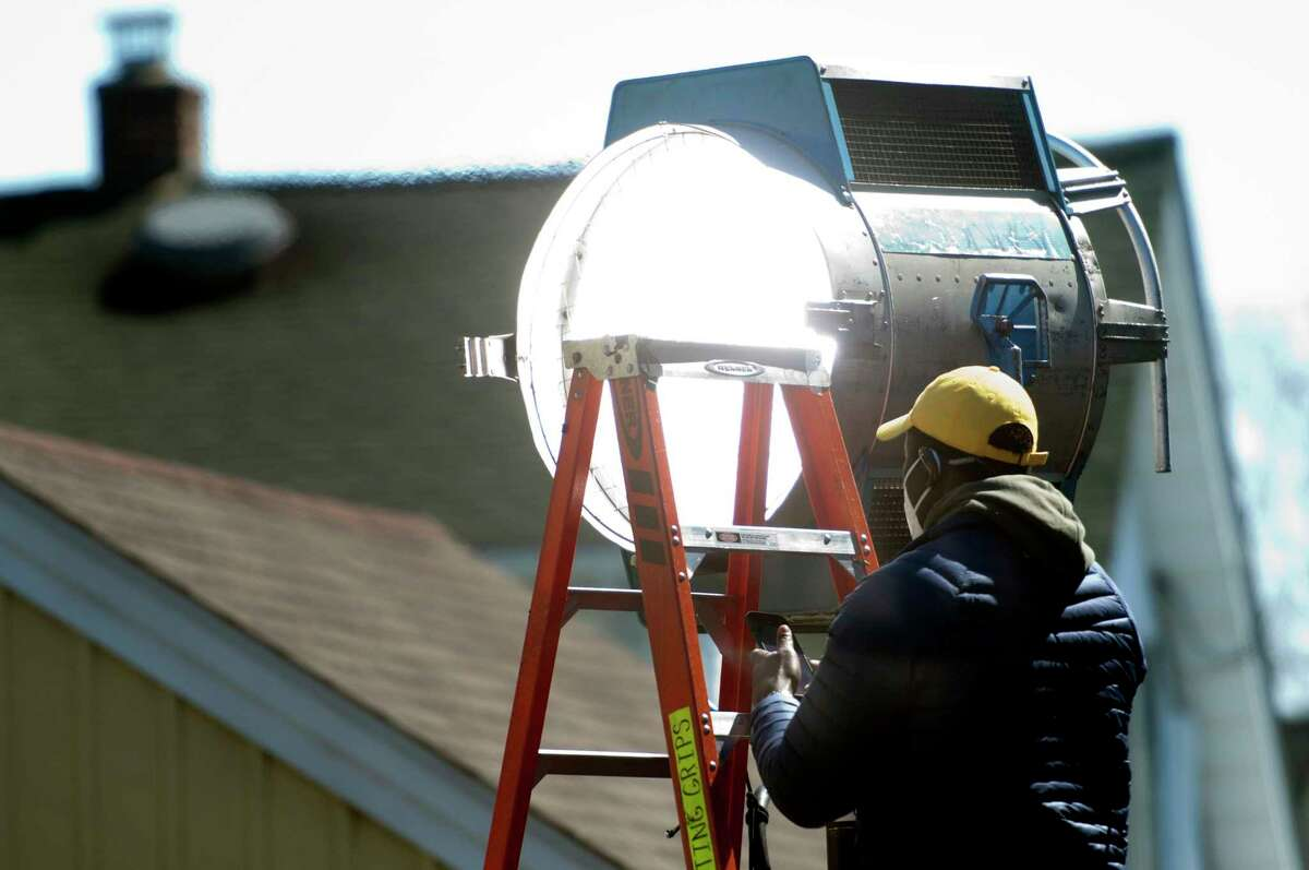 A crew member sets up a light outside a home used as a set for the upcoming Netfix movie The Good Nurse in Stamford, Conn., on Friday April 23, 2021.