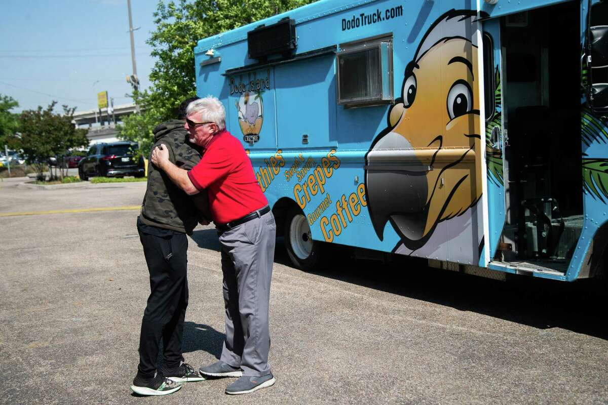 Lucille's 1913 Chef Chris Williams, left, and Jeff Parks, right, embrace as Parks presents Williams with a food truck as a donation to Lucille's 1913, Thursday, April 22, 2021, in Houston. Parks and his brother drove across the country to make the delivery in memory of Parks' nephew.