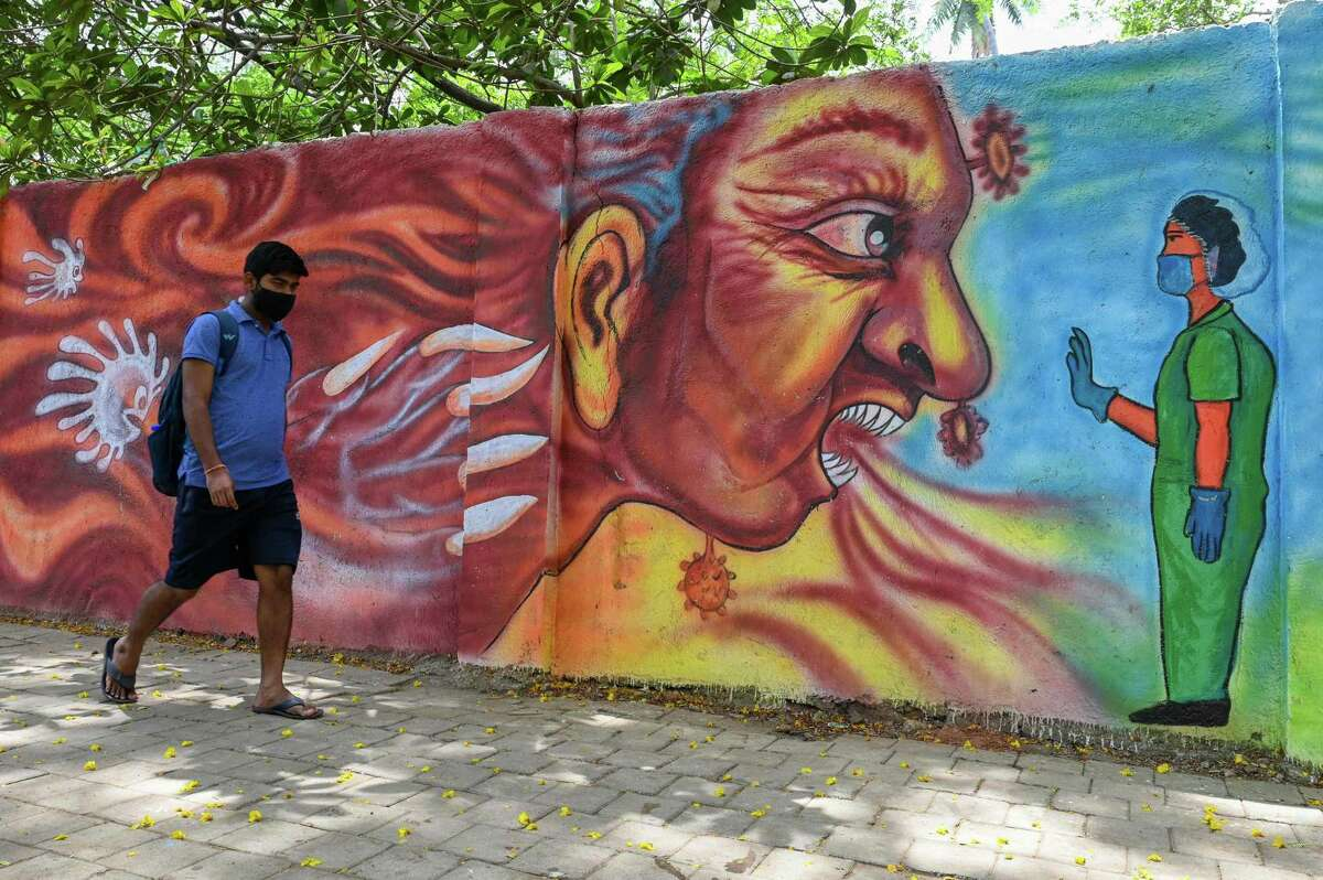 A pedestrian walks past a mural depiciting a health worker stopping the Covid-19 coronavirus, in Mumbai on April 21, 2021 amidst rising Covid-19 coronavirus cases.