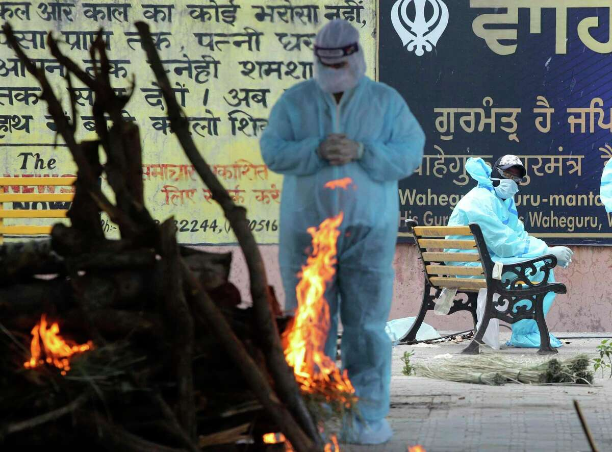 A family member prays as he perform the last rites of a relative who died of COVID-19, at a crematorium in Jammu, India, Friday, April 23, 2021. India's underfunded health system is tattering as the world's worst coronavirus surge wears out the nation. India has confirmed 16 million cases so far, second only to the United States in a country of nearly 1.4 billion people.