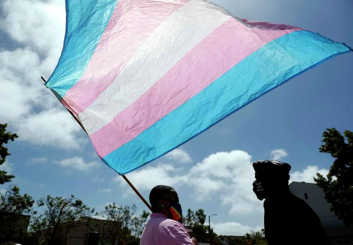 Demonstrators carry a flag representing transgender rights. A reader applauds companies that openly challenge proposals at the Texas Legislature to exclude trans youth from sports.