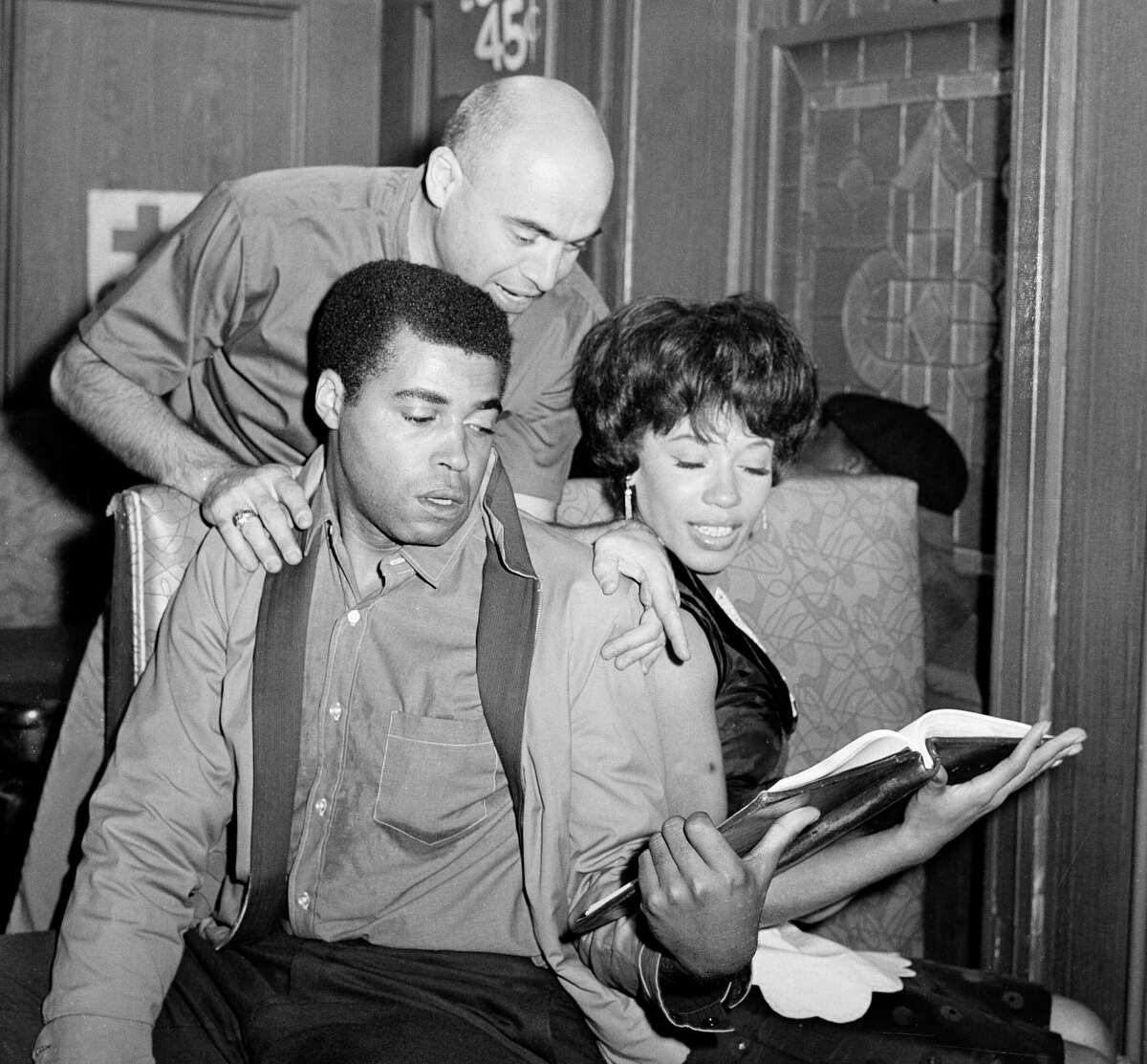 """Director Tom Gries looks over the shoulders as actors James Earl Jones and Diana Sands, go over their lines. Jones and Sands, who play the roles of young lovers in """"Who Do You Kill,"""" an episode of the television series """"East Side-West Side,"""" Sept. 25, 1963. Here, Jones, as Joe, and Sands as Ruth, appear in a scene in a bar in which Ruth works. (AP Photo/Ruben Goldberg)"""