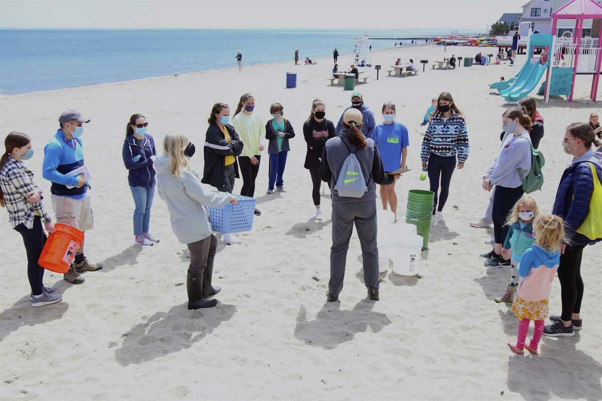 Carrie Rullo, vice president of the Mill River Wetlands Committee, gives directions to participants at the cleanup at Penfield Beach on Sunday, April 18, 2021, in Fairfield, Conn.