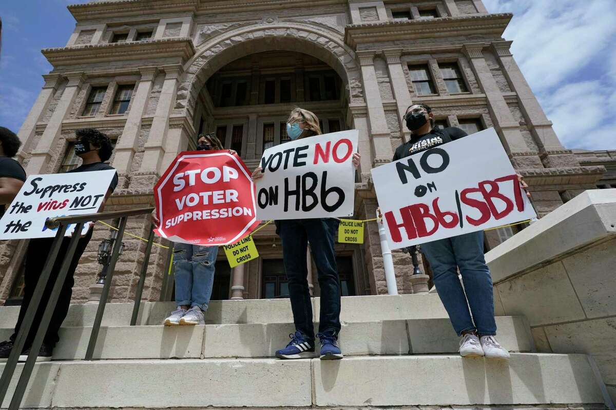 People opposed to Texas voter bills HB6 and SB7 hold signs during a news conference hosted by Texas Rising Action on the steps of the State Capitol, Wednesday, April 21, 2021, in Austin, Texas. (AP Photo/Eric Gay)