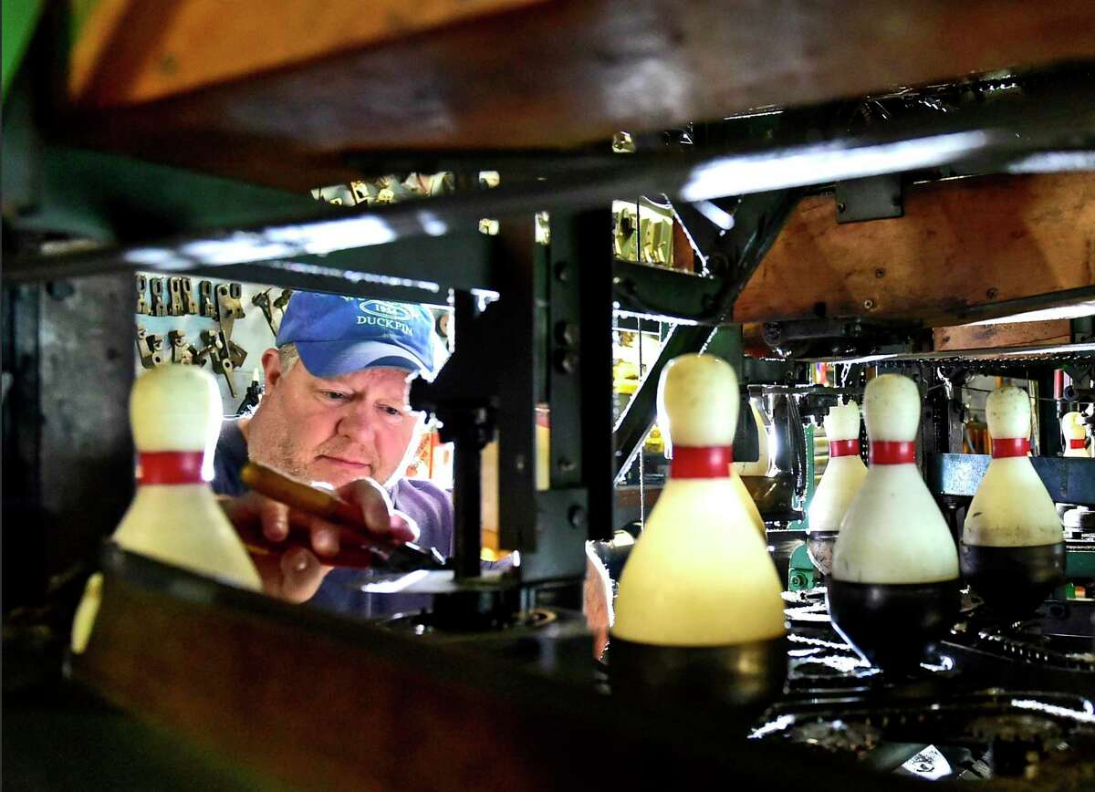 Bob Nugent, owner of the Woodlawn Duckpin bowling lanes in West Haven, checks the iconic mechanical duckpin bowling pinsetter built in the 1950s. Woodlawn has been in business since 1954.