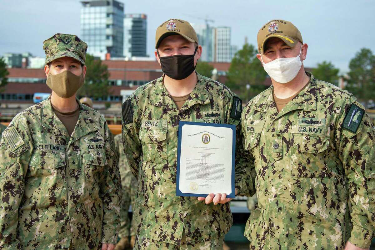 Culinary Specialist 2nd Class Blake Bentz (middle) of Ludington, is awarded Constitution's Sailor of the Quarter by USS Constitution's Commanding Officer Cmdr. John Benda (right) and the Vice Director, Navy Staff Rear Adm. Jacquelyn McClelland. (U.S. Navy Photo/Mass Communication Specialist 3rd Class Alec Kramer/Released)