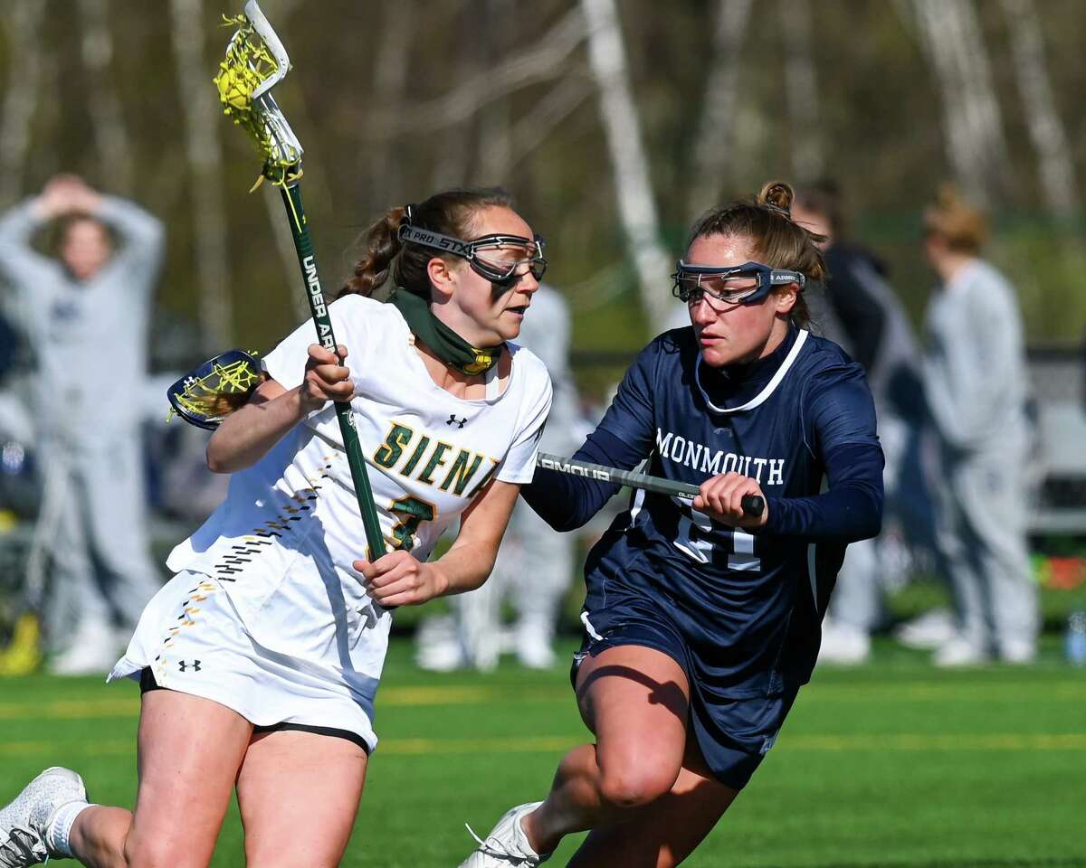 Siena senior Kerry Gerety moves up field in front of Monmouth sophomore Shannon Feeley during a game at Siena College in Loudonville, NY, on Friday, April 23, 2021. (Jim Franco/Special to the Times Union)