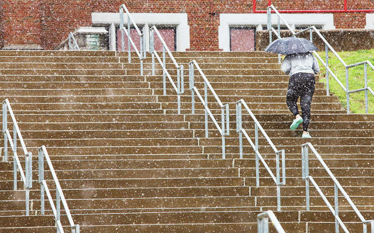 An adult makes their way up the long flight of stairs through the snow Tuesday at Alton Middle School. Temperatures fell all day Tuesday and a hard frost warning is in effect for most of the week. Daytime temperatures fell 40 degrees from Monday afternoon to Tuesday afternoon.