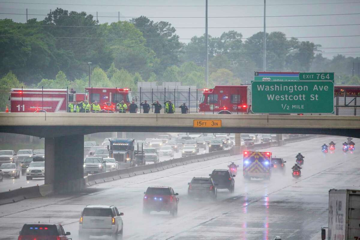 Houston Firefighters pause on the T.C. Jester bridge over I-10 as an escort carried the body of Seguin Firefighter/Paramedic Roger Dean Friday, April 23, 2021, in Houston.