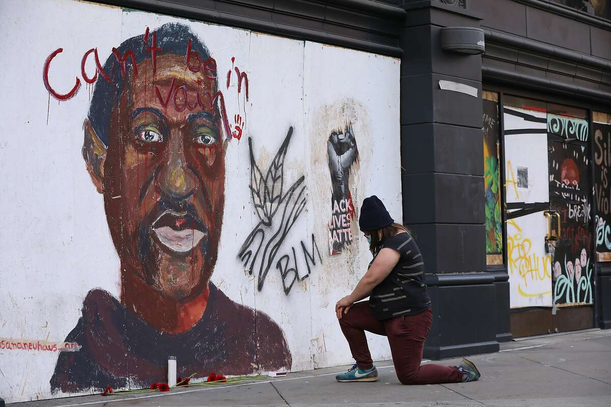 Taylor Ross honors George Floyd by placing flowers and a candle before an Oakland mural of the police shooting victim after a jury convicted his killer.