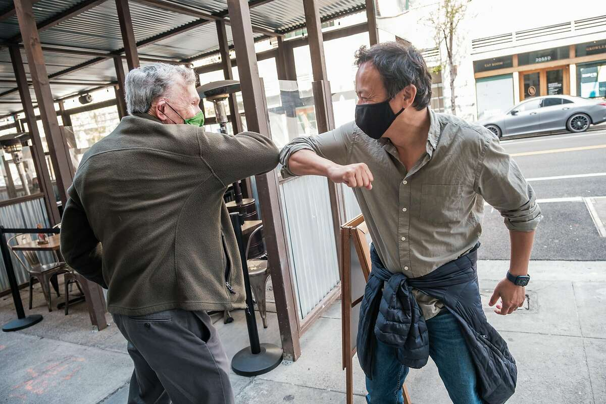 Stephen Shortell (left), former dean of the UC Berkeley School of Public Health, and current dean Dr. Michael Lu greet each other with an elbow bump at a Berkeley restaurant for the first time in more than a year.