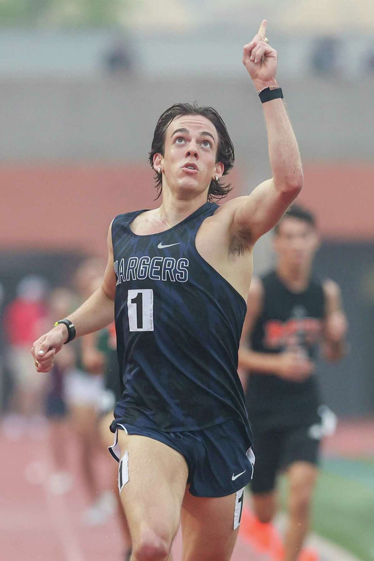 Boerne Champion's Foster Wilfong points to the sky as he crosses the finish line of the 5A boys 3200-meter run during the first day of the Region IV-6A/5A track and field championships at Heroes Stadium on Friday, April 23, 2021. Wilfong won the event with a meet record 9:09.68.
