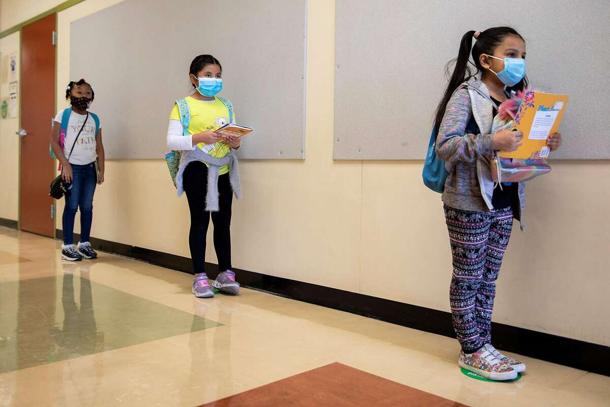 Jaynae Simpson (left), Aracely Garcia-Pablo and Nicole Hernandez line up before heading home after the first day of partial in-person instruction at Garfield Elementary School in Oakland.