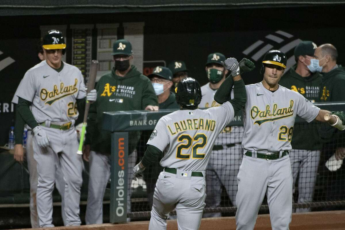 Oakland Athletics' Ramon Laureano (22) celebrates with Matt Olson after hitting a solo home run during the fifth inning of the team's baseball game against the Baltimore Orioles, Friday, April. 23, 2021, in Baltimore. (AP Photo/Tommy Gilligan)