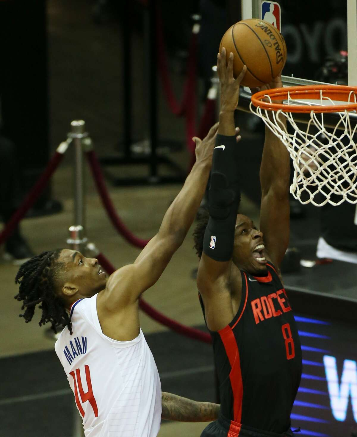 Houston Rockets forward Jae'Sean Tate (8) dunks the ball around LA Clippers guard Terance Mann (14) in the first half of game action at the Toyota Center in Houston on Friday, April 23, 2021.