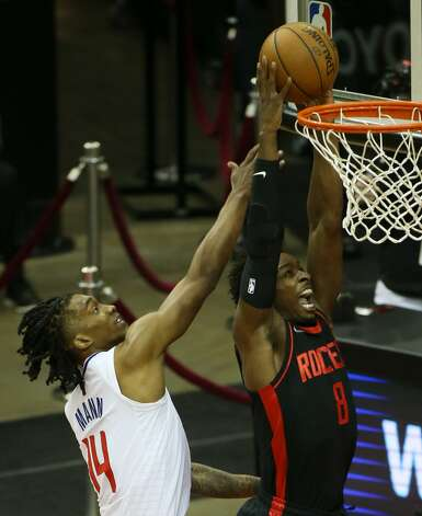 Houston Rockets forward Jae'Sean Tate (8) dunks the ball around LA Clippers guard Terance Mann (14) in the first half of game action at the Toyota Center in Houston on Friday, April 23, 2021. Photo: Elizabeth Conley/Staff Photographer / © 2021 Houston Chronicle