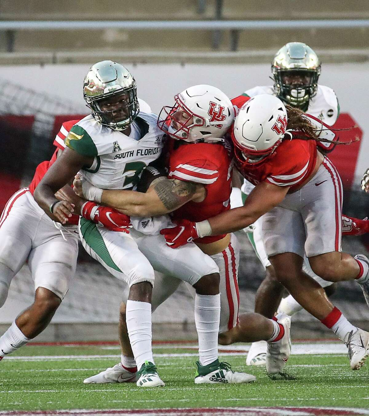 South Florida Bulls quarterback Jordan McCloud (3) is stopped by Houston Cougars defensive lineman Derek Parish (31) and others during the fourth quarter of an NCAA football game Saturday, Nov. 14, 2020, at TDECU Stadium in Houston.