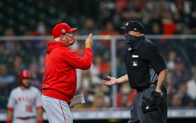 Los Angeles Angels manager Joe Maddon, left, debates an out called against his team with umpire Brian O'Nora, right, during the first inning of an MLB game at Minute Maid Park on Friday, April 23, 2021, in Houston. Photo: Godofredo A Vásquez/Staff Photographer / © 2021 Houston Chronicle
