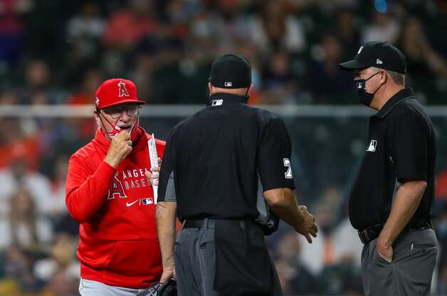 Los Angeles Angels manager Joe Maddon, left, debates an out called against his team with umpire Brian O'Nora, center, during the first inning of an MLB game at Minute Maid Park on Friday, April 23, 2021, in Houston. Photo: Godofredo A Vásquez/Staff Photographer / © 2021 Houston Chronicle