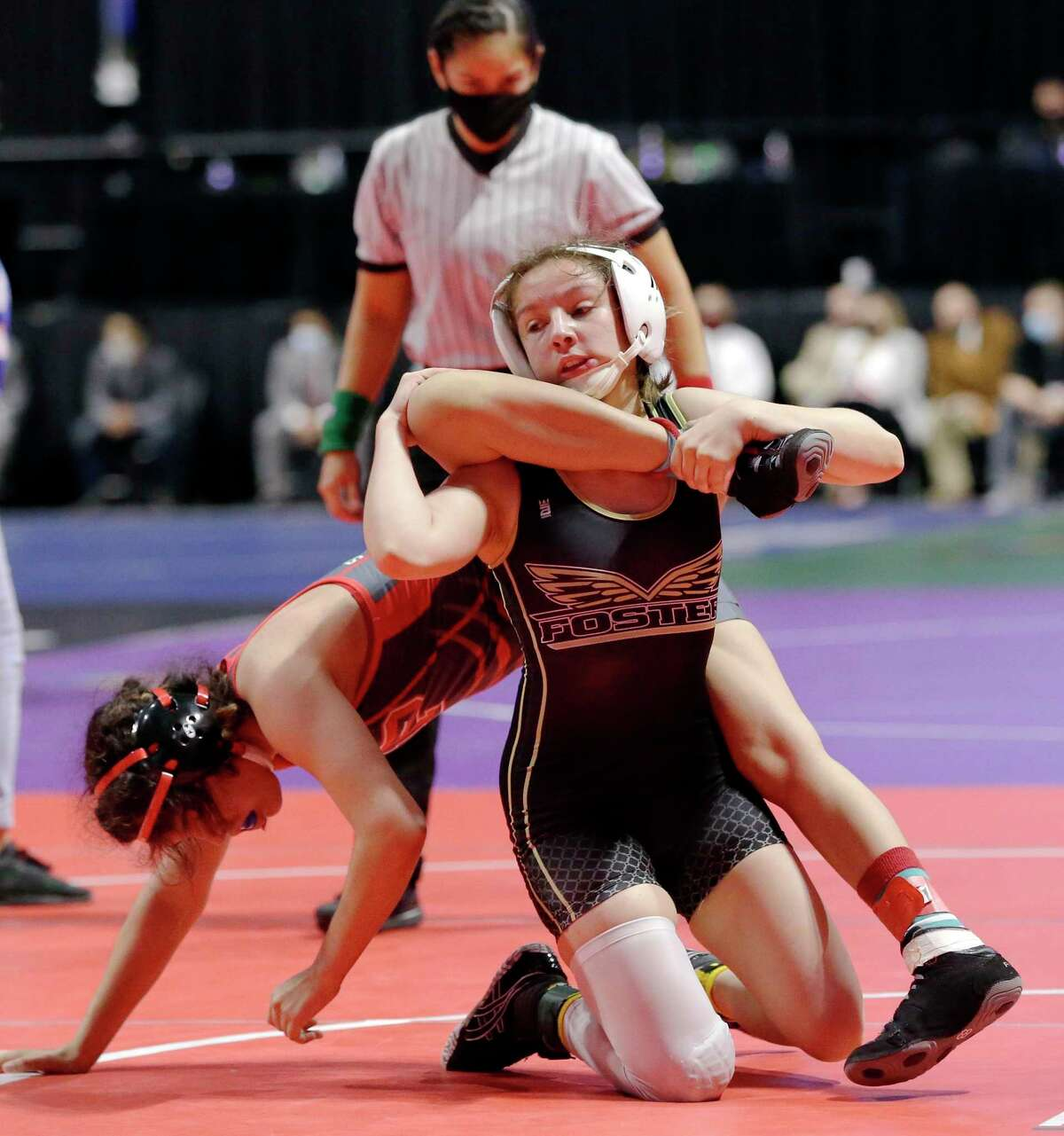 Emily Trevino with Mission Sharyland Pioneer, left, is taken down by Madison Canales with Richmond Foster, right, in the 119 weight class of the UIL Girls 5A State Wrestling Championships Friday, Apr. 23, 2021 at the Berry Center in Cypress, TX.