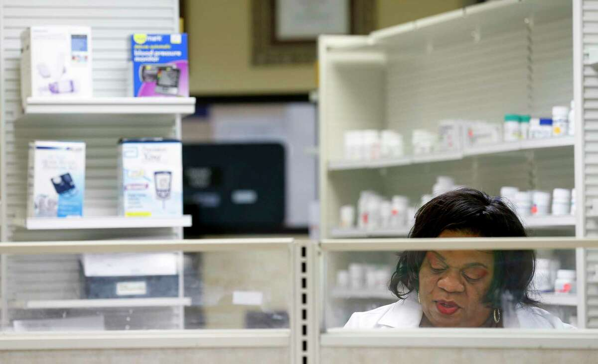 Dr. Anjanette Wyatt, right, fills prescriptions for clients inside Clinical Care Pharmacy.