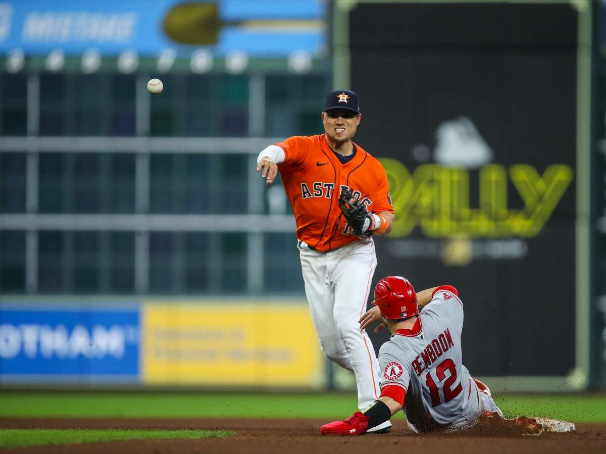 Houston Astros second baseman Aledmys Diaz (16) turns a double play against the Los Angeles Angels during the seventh inning of an MLB game at Minute Maid Park on Friday, April 23, 2021, in Houston.