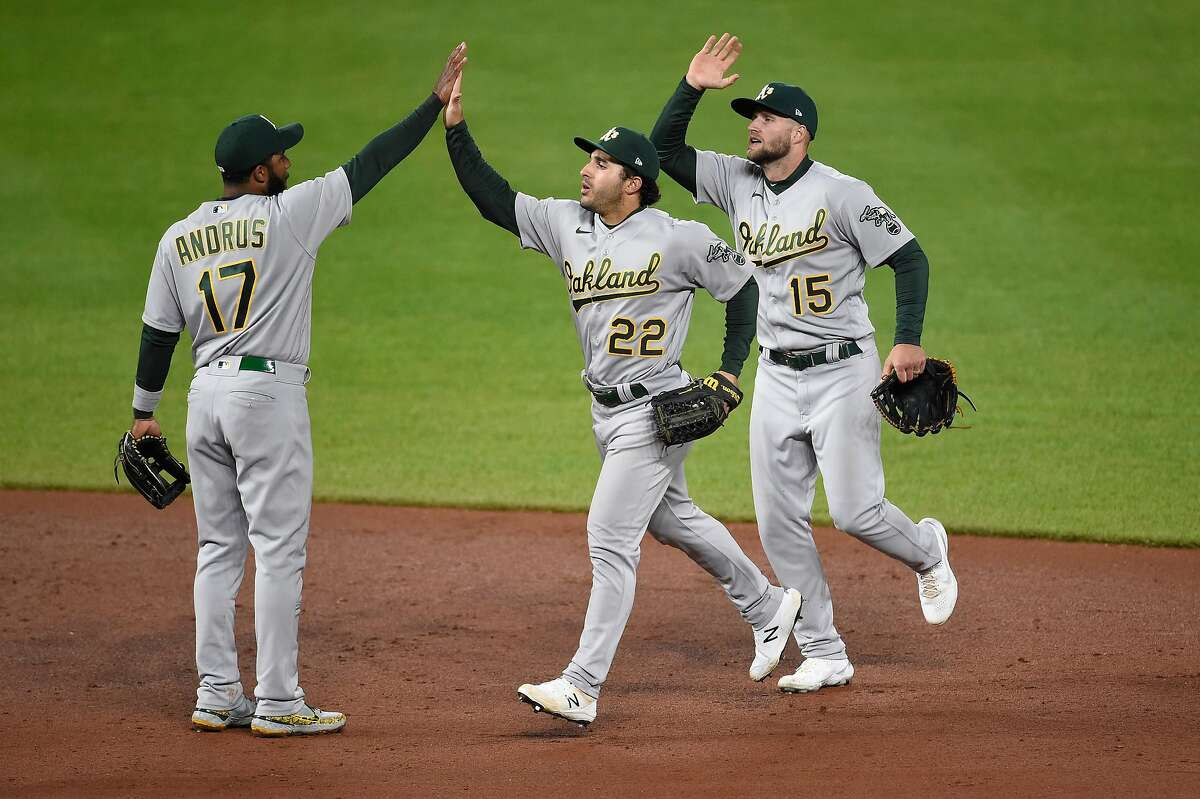 A's shortstop Elvis Andrus (17) celebrates with Ramón Laureano (22) and Seth Brown after their win in Baltimore.