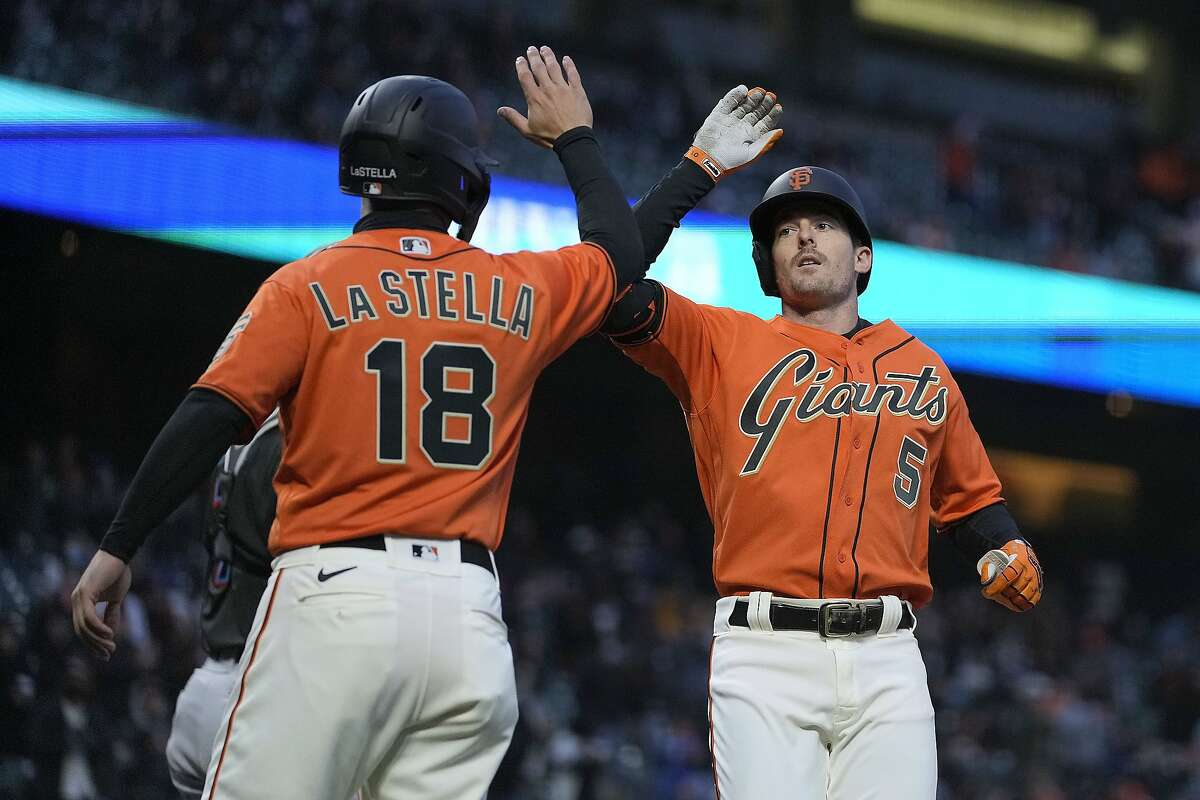 San Francisco Giants' Mike Yastrzemski (5) high fives teammate Tommy La Stella (18) after hitting a two run home run against the Miami Marlins during the third inning of a baseball game on Friday, April 23, 2021, in San Francisco. (AP Photo/Tony Avelar)