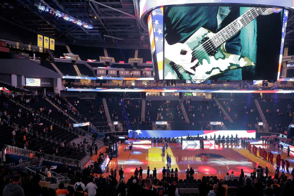 Fans listen to the national anthem as they returned to the arena in limited numbers for the first time in 409 games before the Golden State Warriors played the Denver Nuggets at Chase Center in San Francisco, Calif., on Friday, April 23, 2021.