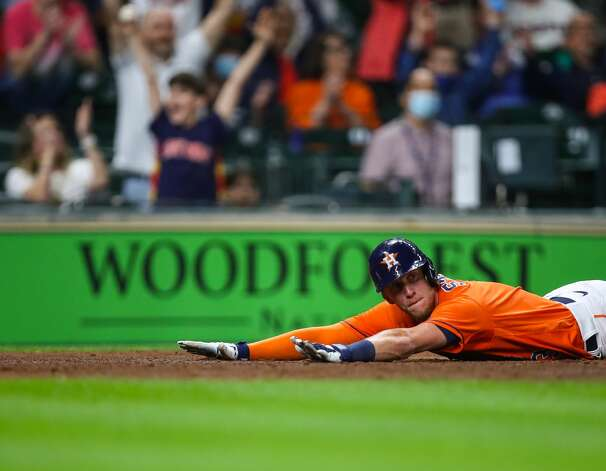 Houston Astros center fielder Myles Straw (3) remains on the floor for a few moments after sliding safely at home plate on a sacrifice fly hit by shortstop Carlos Correa (1) during the 10th inning of an MLB game against the Los Angeles Angels at Minute Maid Park on Friday, April 23, 2021, in Houston. The Astros won 5-4. Photo: Godofredo A Vásquez/Staff Photographer / © 2021 Houston Chronicle