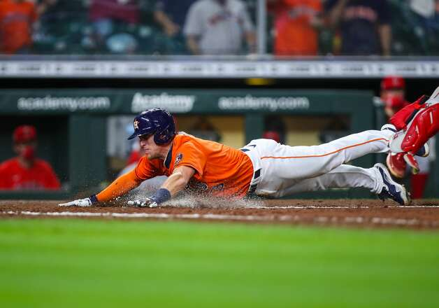 Houston Astros center fielder Myles Straw (3) slides safely at home plate after tagging from third base on a sacrifice fly hit by shortstop Carlos Correa (1) during the 10th inning of an MLB game against the Los Angeles Angels at Minute Maid Park on Friday, April 23, 2021, in Houston. The Astros won 5-4. Photo: Godofredo A Vásquez/Staff Photographer / © 2021 Houston Chronicle