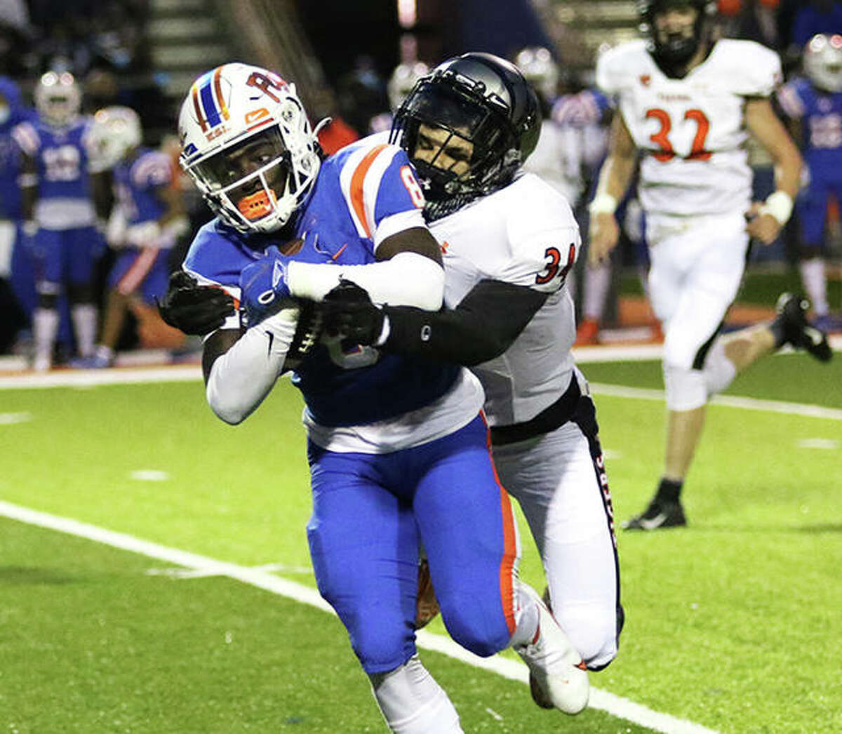Edwardsville's DeShawn Larson catches East St. Louis' Kenneth Cotton to make a tackle Friday night at Jordan Stadium in East St. Louis.