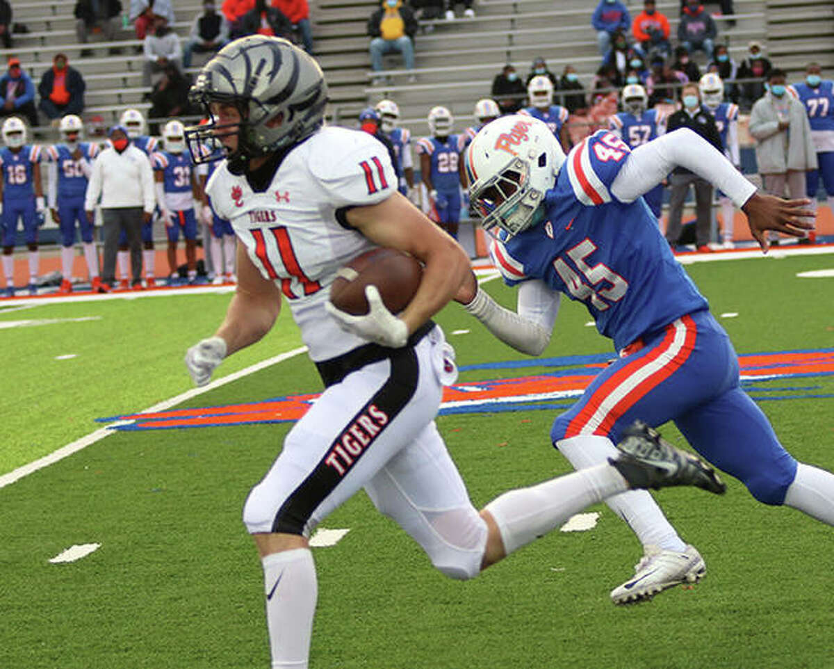 Edwardsville's Mason Ahlers (left) breaks into the open at midfield and outruns the Flyers to the end zone for a 74-yard TD return of the game's opening kickoff Friday night at Jordan Stadium in East St. Louis.