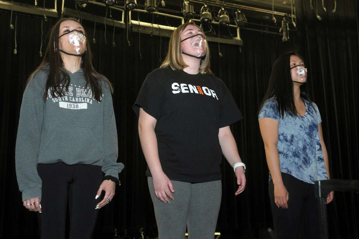 From left, seniors Brooke Doolan, Megan McCarthy and Caidyn Collins sing during a rehearsal for the Shelton High School drama club's upcoming musical review, seen here in Shelton Conn. April 22, 2021.