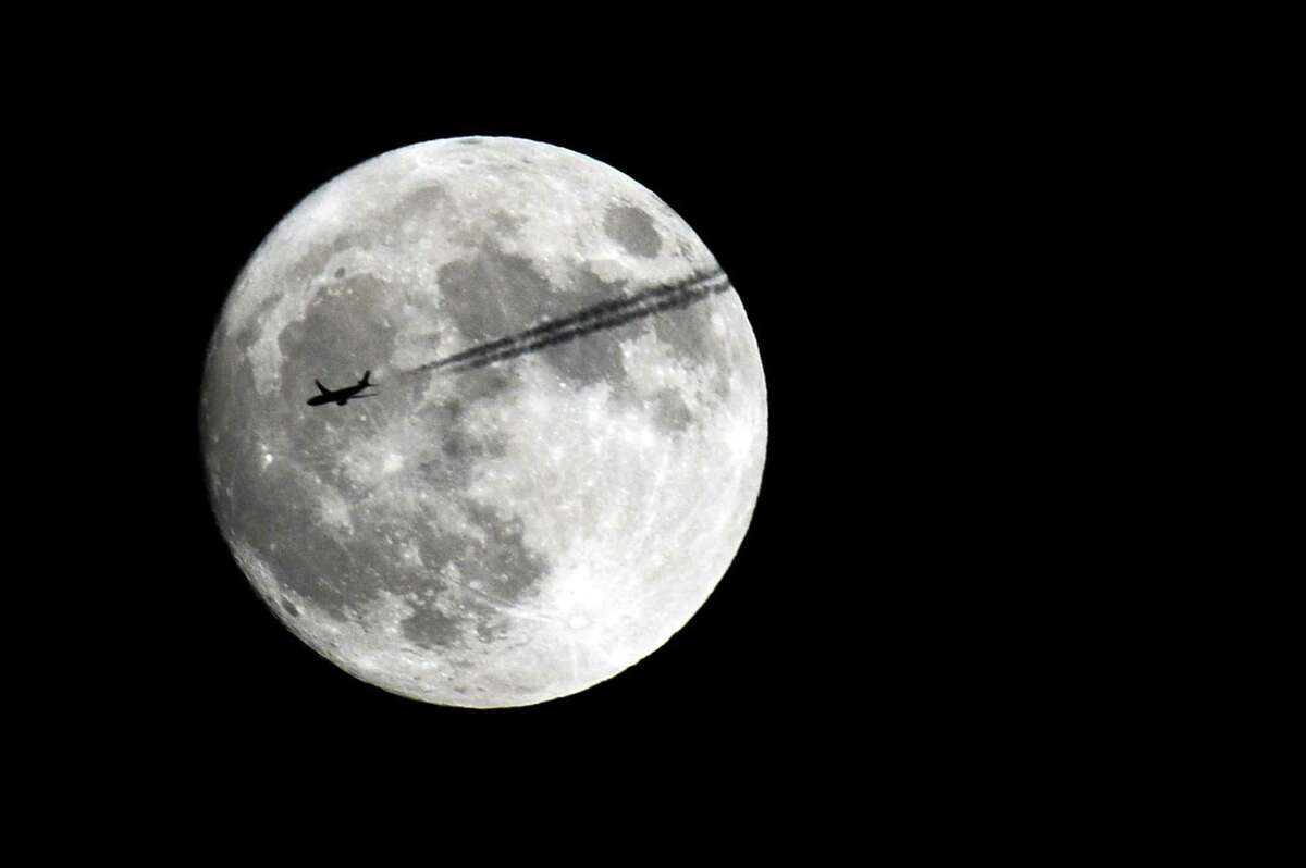 An airplane flies past the moon, taken from Stamford, Conn., on Sunday, Nov. 13, 2016.