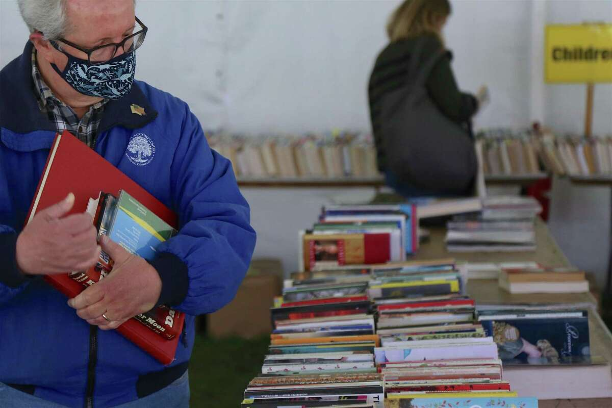 John Balint, of Stratford, a longtime book sale attendee, looks over some books at the Pequot Library's Sping Fling Book Sale on Friday, April 23, 2021, in Fairfield, Conn.