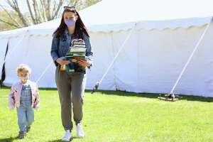 Krissy Dingle, of Fairfield and her daughter Birdie, 2, carry home their purchases at the Pequot Library's Sping Fling Book Sale on Friday, April 23, 2021, in Fairfield, Conn.