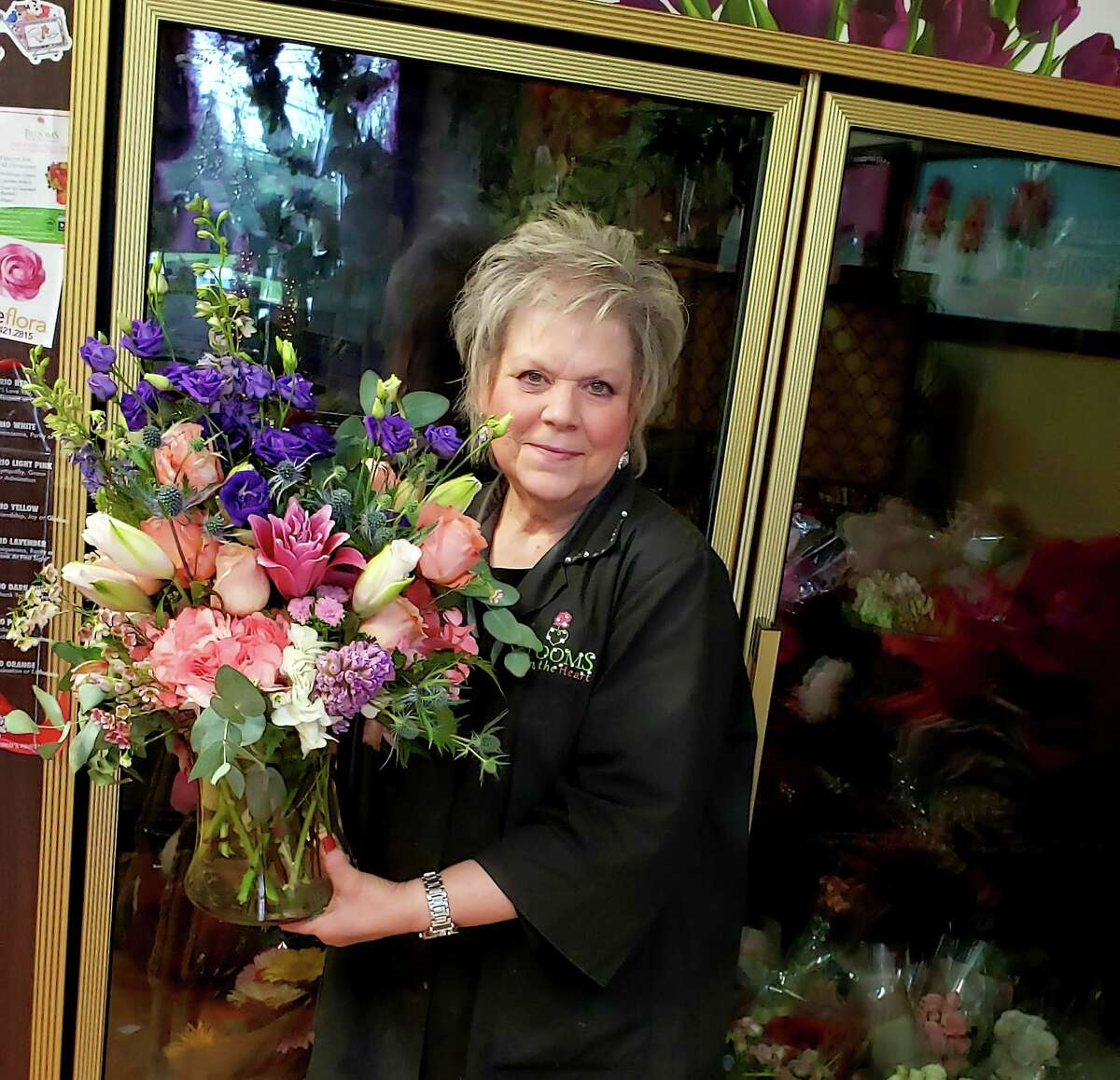"""Lana King is happy these days just to turn on the """"We're OPEN"""" sign in her shop after a roller coaster year with the pandemic. King owns and operates Blossoms from the Heart in Cypress and loves sharing her custom arrangements with the community."""