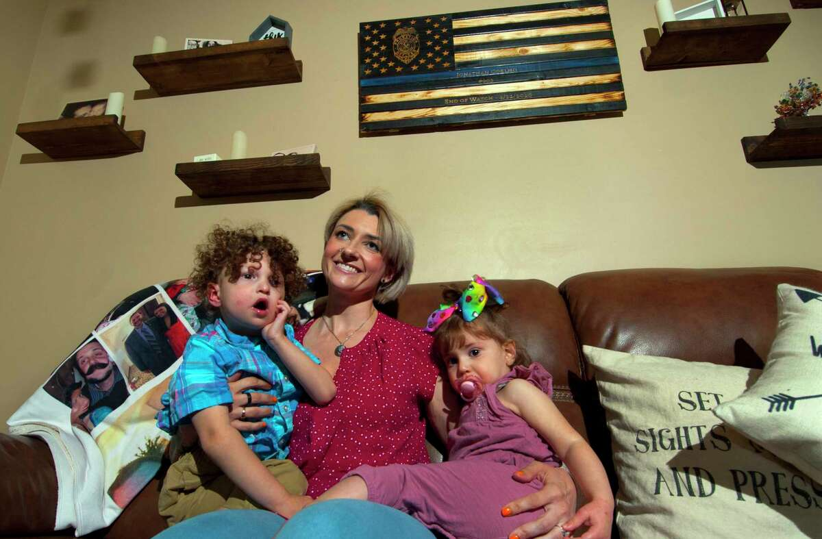 Katie Coelho poses with her children Braedyn, 3, left, and Penelope, 22 months, at her home in Southbury, Conn., on Thursday April 22, 2021. Thursday marks the one-year anniversary of her husband Jonathan Coelho's death from COVID-19.