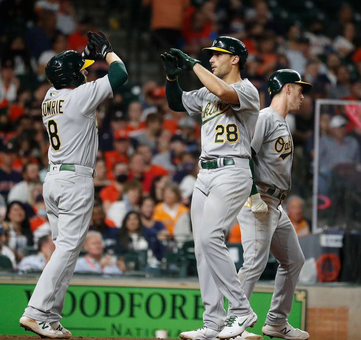 Oakland Athletics Matt Olson (28) celebrates his three-run home with Jed Lowrie (8) during the eighth inning of an MLB baseball game at Minute Maid Park, in Houston, Friday, April 9, 2021.