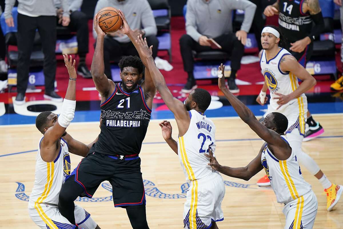 Philadelphia 76ers' Joel Embiid, second from left, tries to pass the ball against Golden State Warriors' Kevon Looney, from left, Andrew Wiggins and Draymond Green during the second half of an NBA basketball game, Monday, April 19, 2021, in Philadelphia. (AP Photo/Matt Slocum)