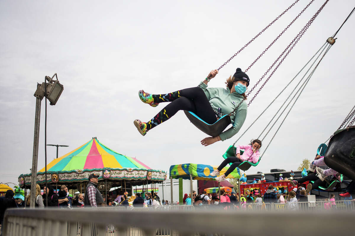 Riley Jimenez of Saginaw, 15, sits back on a swing as families enjoy carnival rides, games, food and prizes at the annual Freeland Walleye Festival Saturday, April 24, 2021 at Burt Watson Chevrolet in Freeland. (Katy Kildee/kkildee@mdn.net)