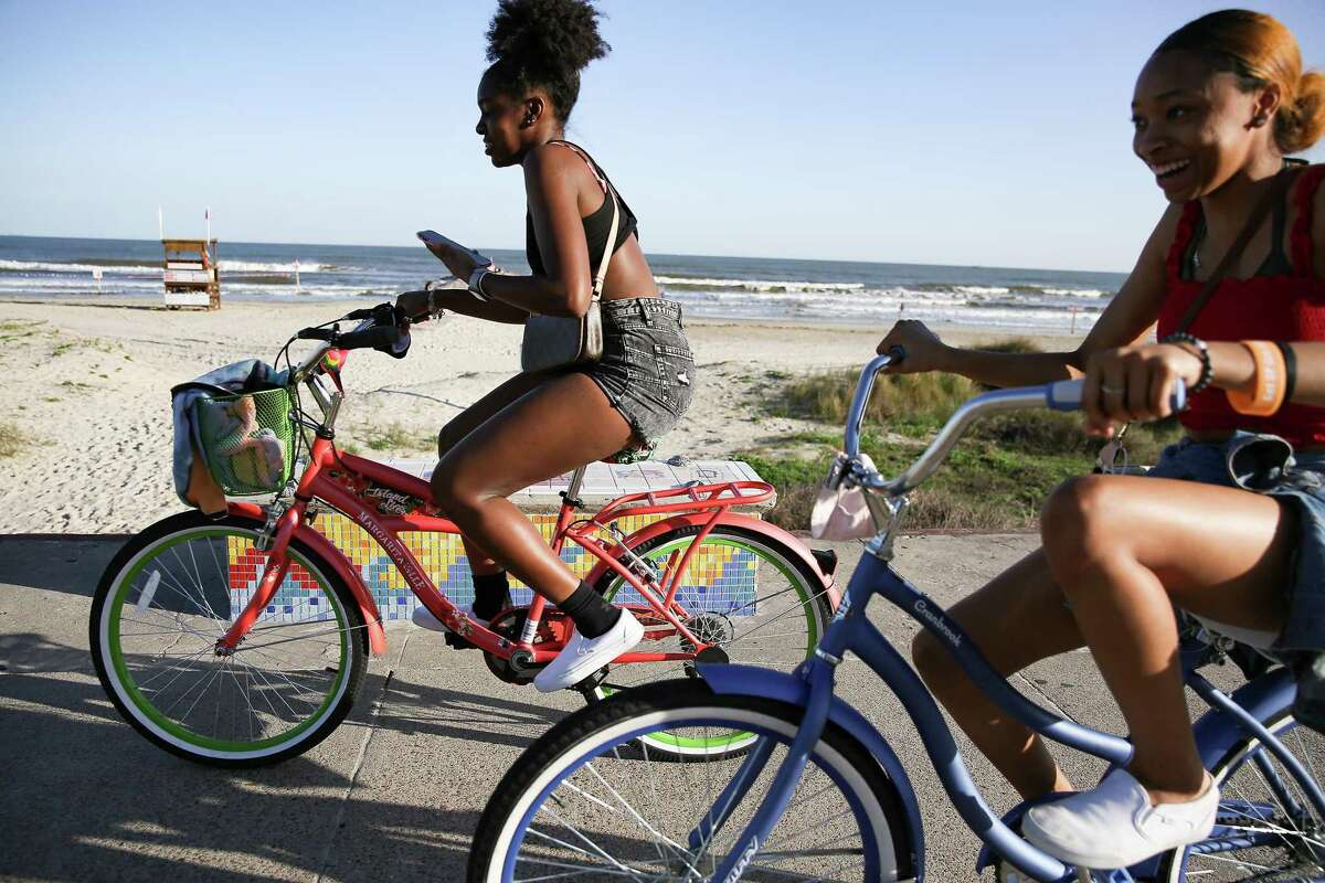 Cyclist ride along the Seawall in Galveston on March 17, 2021.