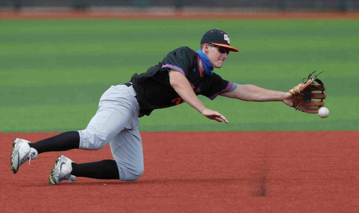 FILE - Grand Oaks third baseman AJ McGrady (24) tries to make a play on a hit by Edgar Quintero #11 of Cypress Creek during the fourth inning of a non-district high school baseball game at Grand Oaks High School, Saturday, March 13, 2021, in Spring. Martin was charged with an error on the play.