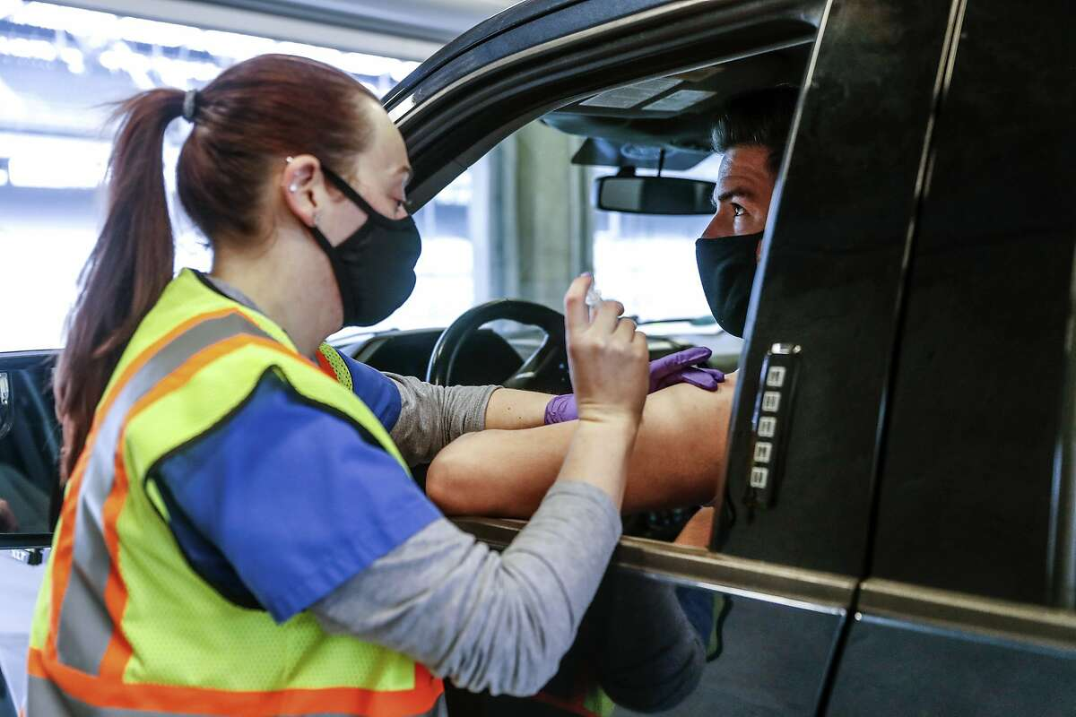 Pharmacy technician Synclaire Anderson vaccinates Joe Freed with a Johnson & Johnson shot at the Indianapolis Motor Speedway in Indianapolis. With a green light from federal health officials, several states now have resumed use of the one-shot coronavirus vaccine.
