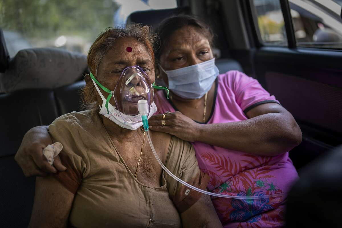 A COVID-19 patient receives oxygen inside a car provided by a Gurdwara, a Sikh house of worship, in New Delhi, India, Saturday, April 24, 2021.